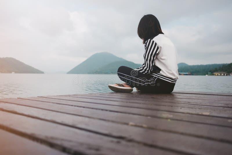 Junge Frau sitzen allein auf Holzbrücke hat Fluss, Berg, Himmel stockfoto