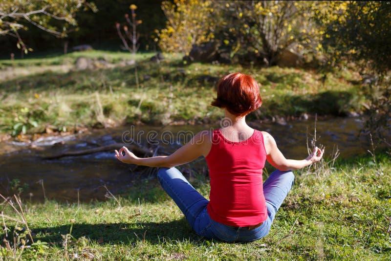 Junge Frau sitzt auf der Küste von einem kleinen Fluss und meditiert an einem sonnigen Herbsttag lizenzfreies stockbild