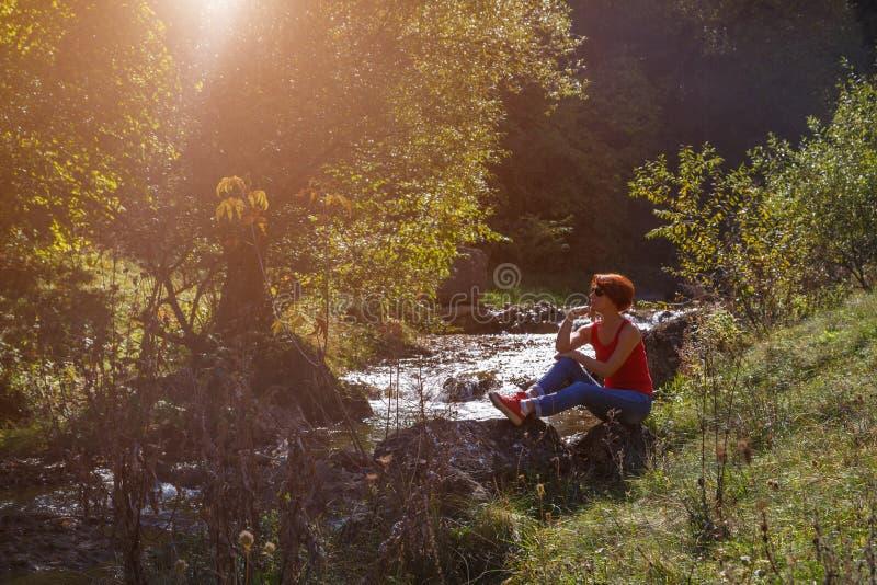Junge Frau sitzt auf einem Stein nahe einem kleinen Strom an einem sonnigen Herbsttag stockbild