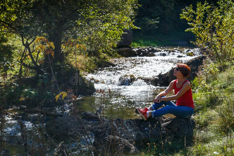 Junge Frau sitzt auf einem Stein nahe einem kleinen Strom an einem warmen Herbsttag stockbild