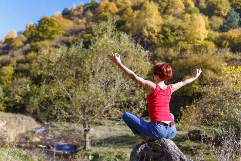 Junge Frau sitzt auf einem Stein und meditiert vor dem hintergrund eines Flusses, eines Waldes und eines blauen Himmels an einem  lizenzfreie stockfotografie