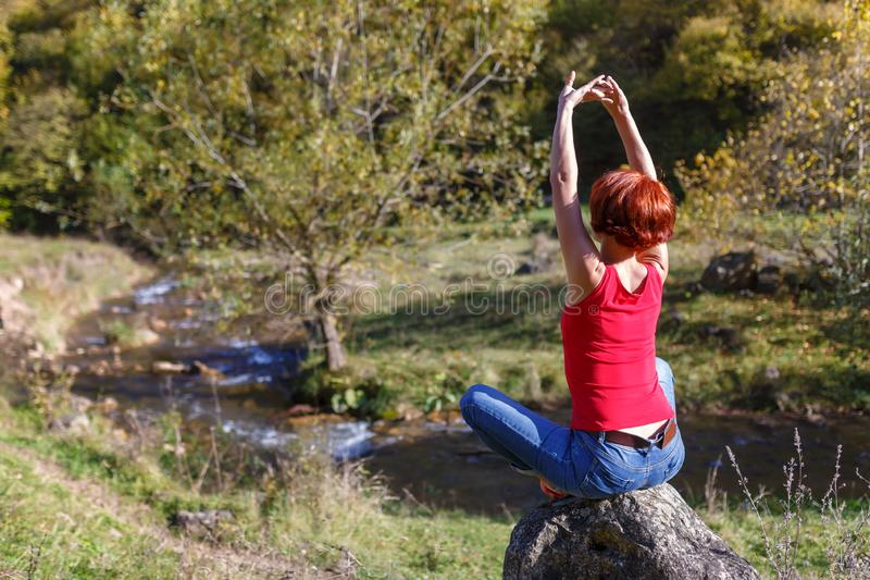 Junge Frau sitzt auf einem Stein und meditiert vor dem hintergrund eines Flusses und eines Waldes an einem sonnigen Herbsttag stockbild