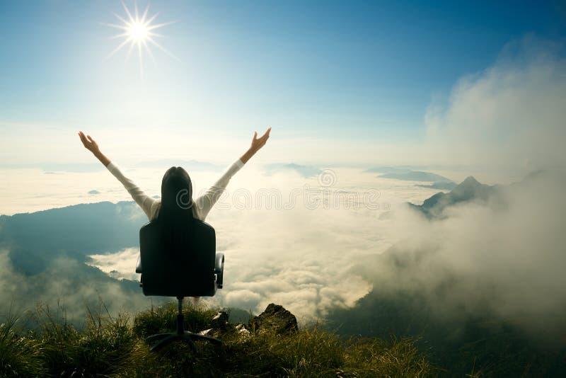 Junge Frau sitzt auf einem Stuhl und öffnet ihre Arme lizenzfreie stockbilder