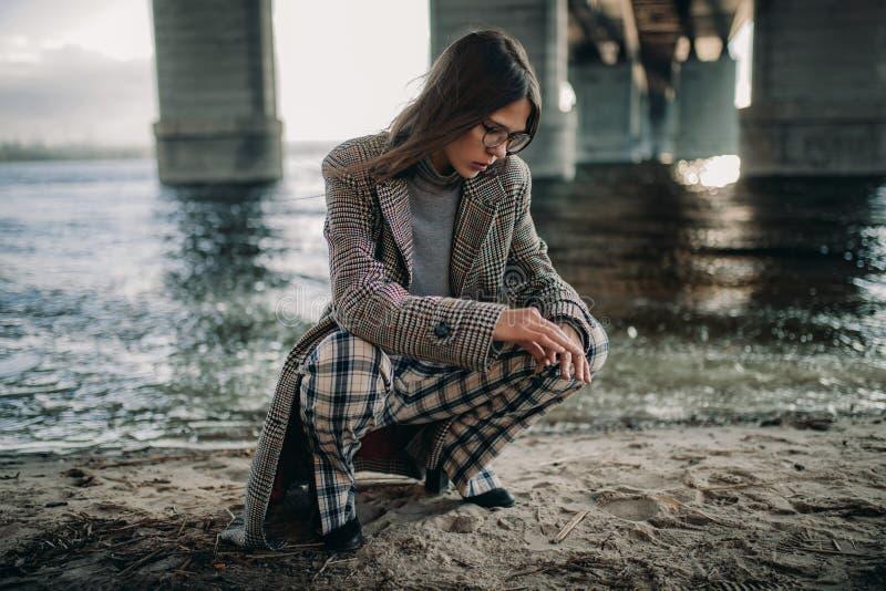 Junge Frau sitzt auf Flussbank unter Brücke lizenzfreie stockfotos