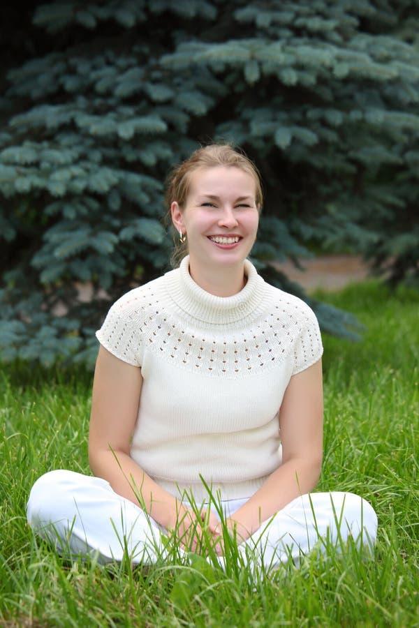 Junge Frau sitzt auf Gras stockfotografie