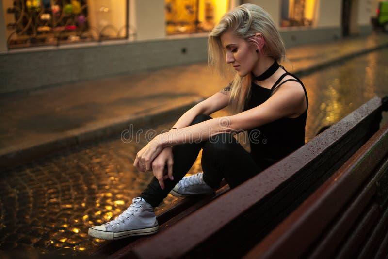 Junge Frau sitzt auf nasser Bank auf Stadtstraße am Abend im Regen lizenzfreie stockbilder