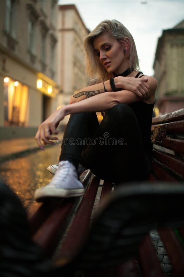 Junge Frau sitzt auf nasser Bank auf Stadtstraße am Abend im Regen lizenzfreie stockfotos