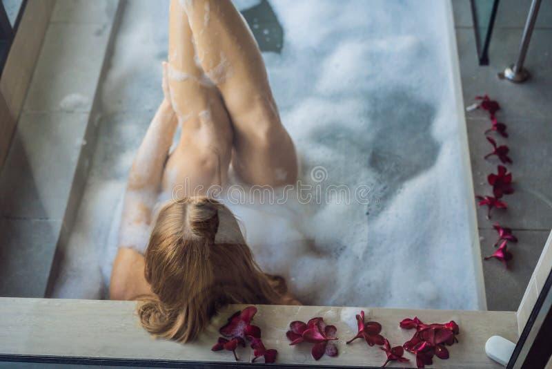 Junge Frau sitzt in einem Bad mit Schaum- und Frangipaniblumen vor dem hintergrund einer panoramischen Fensterunterlassung lizenzfreie stockbilder