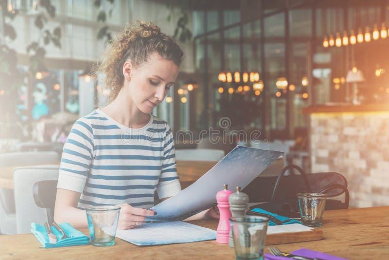 Junge Frau sitzt im Café am Holztisch und am Ablesen Mädchen wartet auf Freunde, Kollegen im Restaurant lizenzfreie stockbilder
