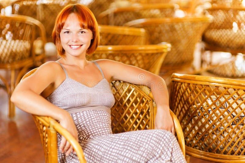 Junge Frau sitzt im Lehnsessel stockbild