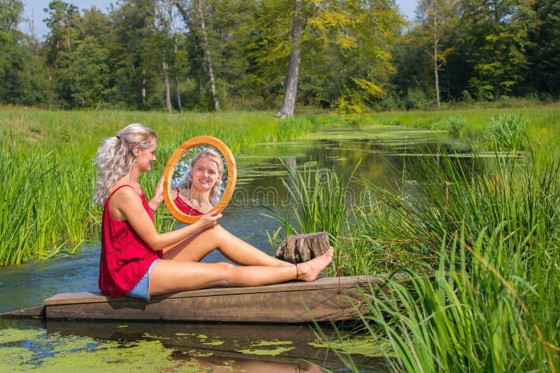 Junge Frau sitzt mit Spiegel am Wasser in der Natur stockbilder
