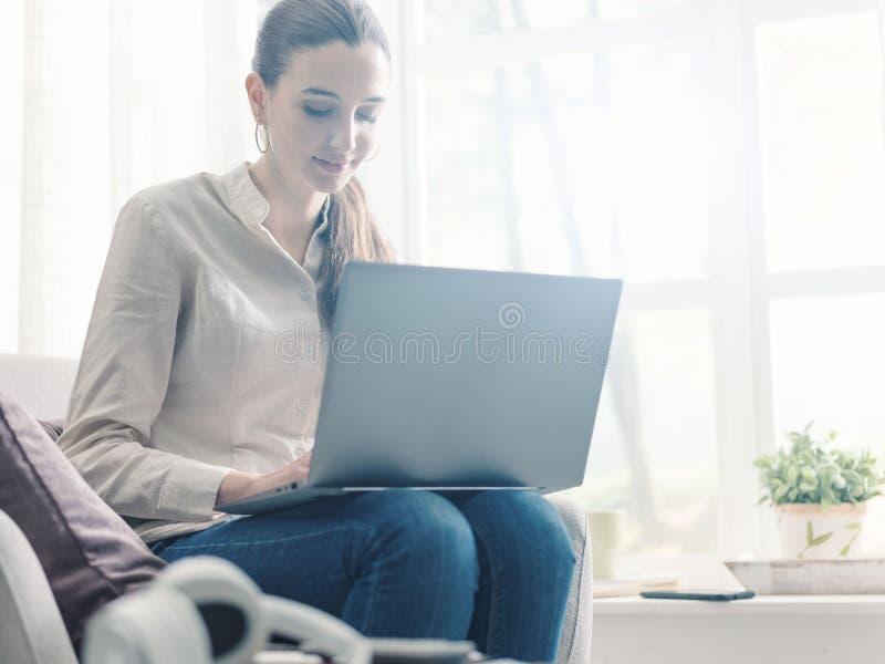 Junge Frau sitzt neben einem Fenster und verbindet sich mit ihrem Laptop lizenzfreie stockfotos
