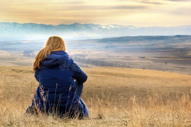 Junge Frau sitzt und betrachtet die Schnee-mit einer Kappe bedeckten Berge stockfotos