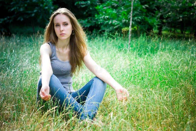 Junge Frau sitzt und betrachtet Kamera stockfotografie