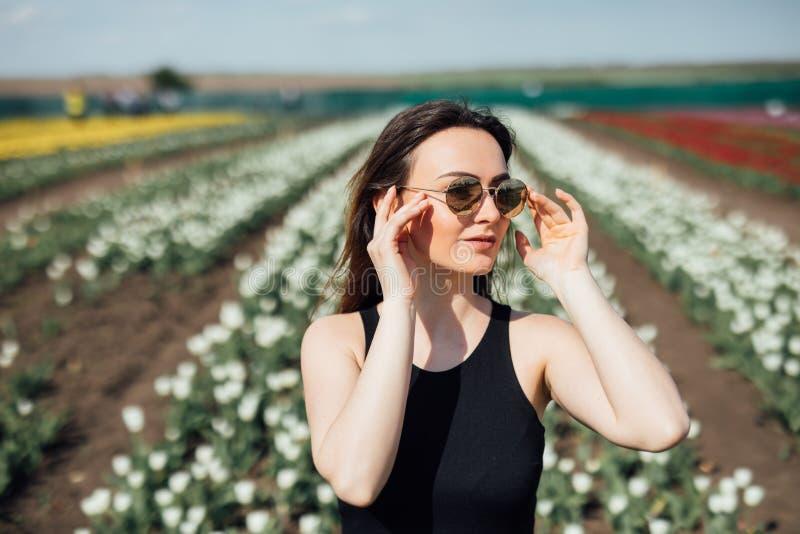 Junge Frau am sonnigen Tag der Sonnenbrille im Frühjahr auf Tulpen Blumenfeld Mutter`s Tag frühjahr stockfotos