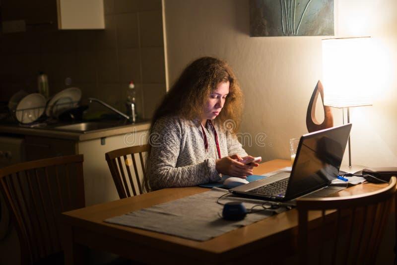 Junge Frau spät nachts simsend unter Verwendung des Handys schläfrig und müde im Internet-Kommunikationsüberbeanspruchungskonzept stockfotografie