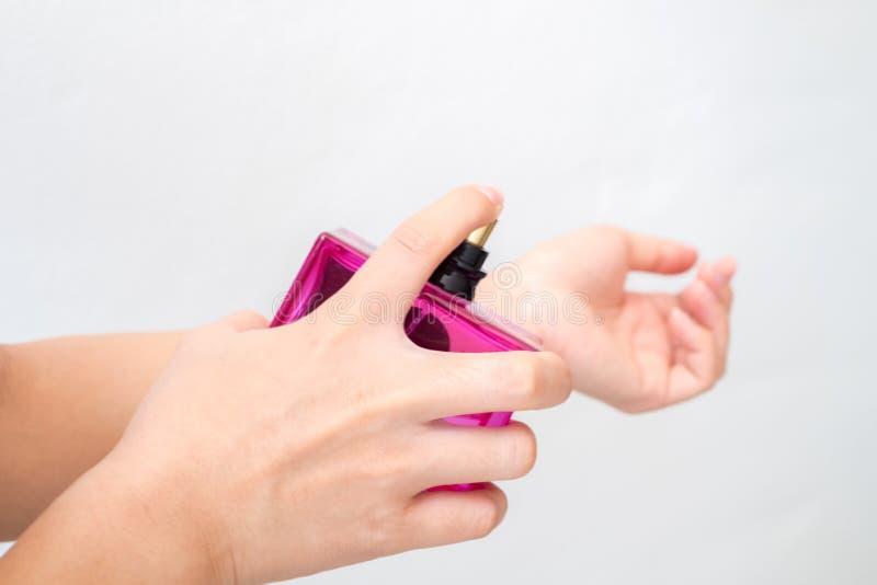 Junge Frau sprüht Parfüm auf seinem Handgelenk lizenzfreies stockfoto