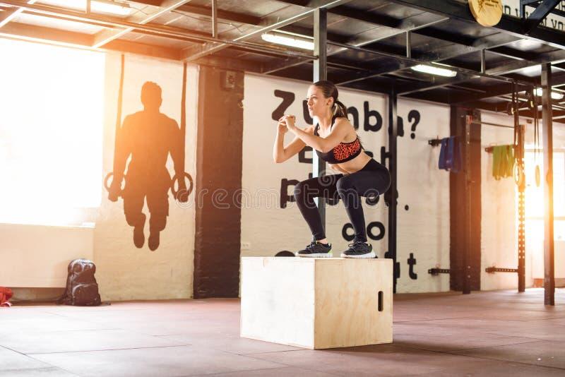 Junge Frau springt auf Kasten stockfoto