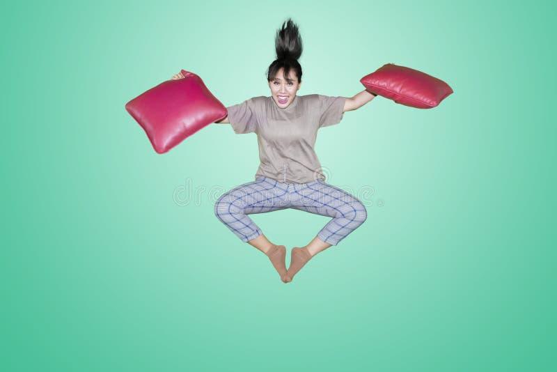 Junge Frau springt mit roten Kissen stockfotografie
