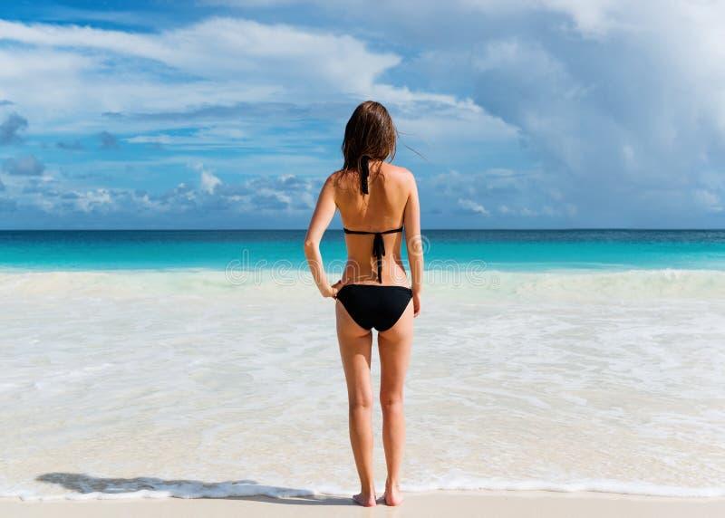 Junge Frau steht auf dem Strand lizenzfreies stockbild