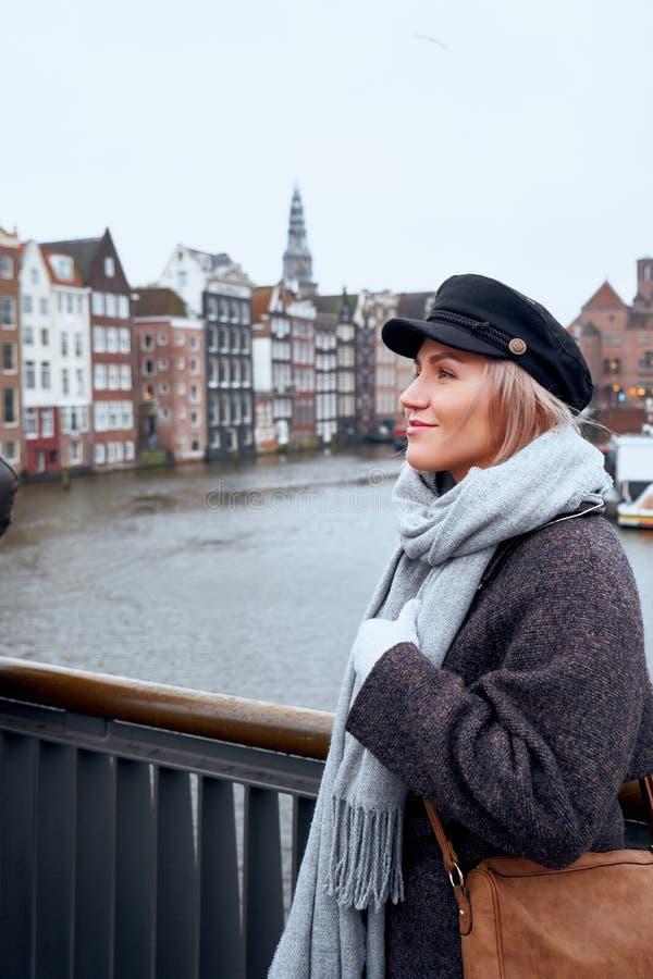 Junge Frau steht auf der Brücke und betrachtet den Kanal von Amsterdam, die Niederlande stockbild