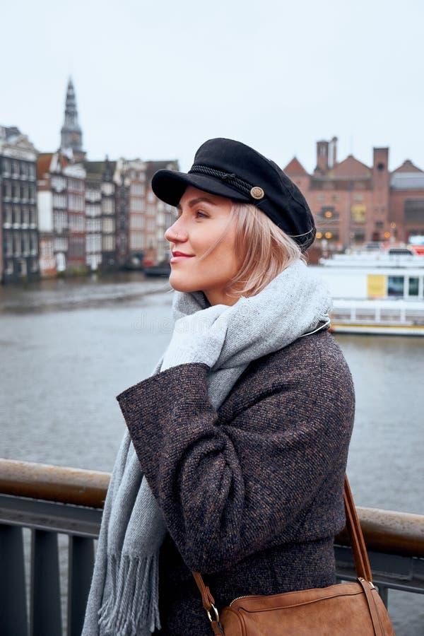 Junge Frau steht auf der Brücke und betrachtet den Kanal von Amsterdam, die Niederlande stockfoto