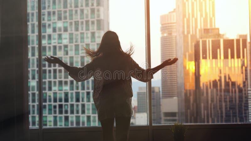 Junge Frau steht die großen Fensterausdehnungsarme und das Haar und ihre Wohnung auf den Stadtgebäuden heraus schauen während ber lizenzfreies stockfoto
