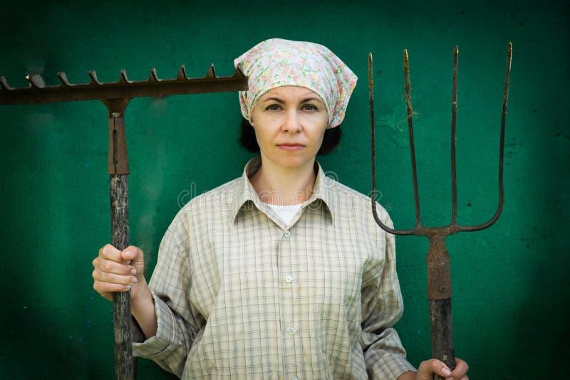 Junge Frau steht mit einer Heugabel nahe einem Stall auf einer Ranch lizenzfreie stockfotografie