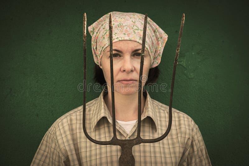 Junge Frau steht mit einer Heugabel nahe einem Stall auf einer Ranch stockfoto