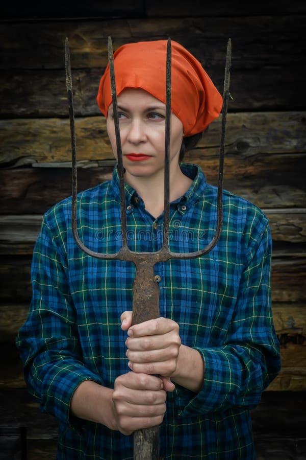 Junge Frau steht mit einer Heugabel nahe einem Stall auf einer Ranch stockbild