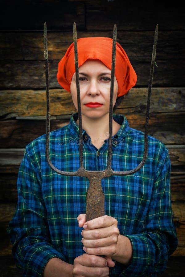 Junge Frau steht mit einer Heugabel nahe einem Stall auf einer Ranch lizenzfreies stockfoto