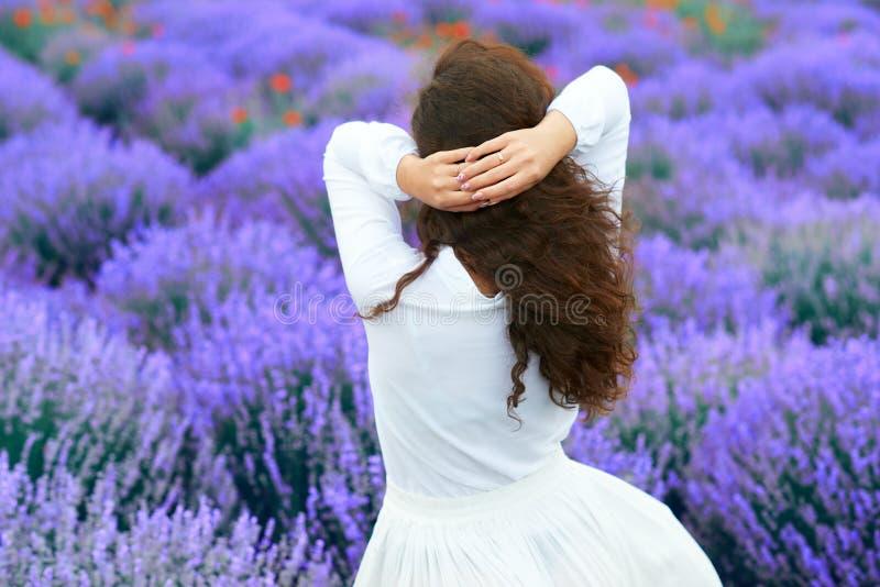Junge Frau steht zurück auf dem Lavendelblumengebiet, schöne Sommerlandschaft stockbilder