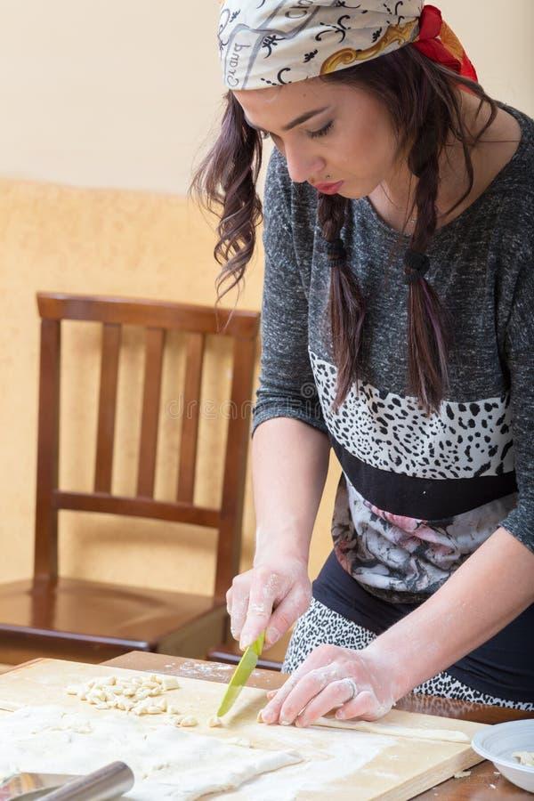 Junge Frau stellt die gnocchetti Teigwaren her stockbilder