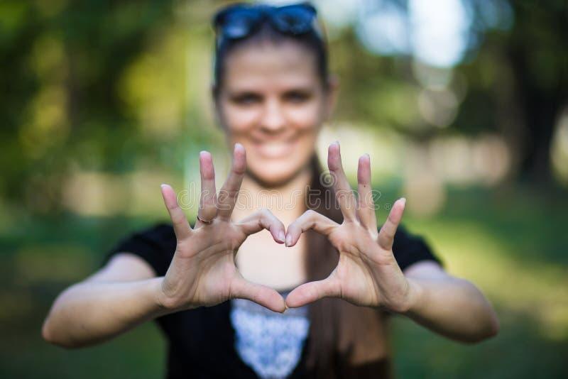 Junge Frau stellt Hände in Form vom Liebesherzen her stockfotografie
