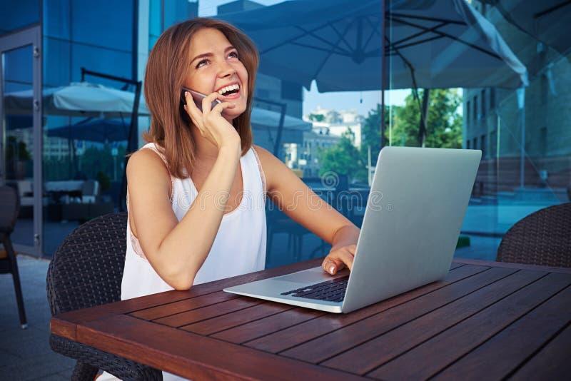 Junge Frau in Straße café unter Verwendung ihres Laptops und Unterhaltung auf mobi lizenzfreie stockbilder