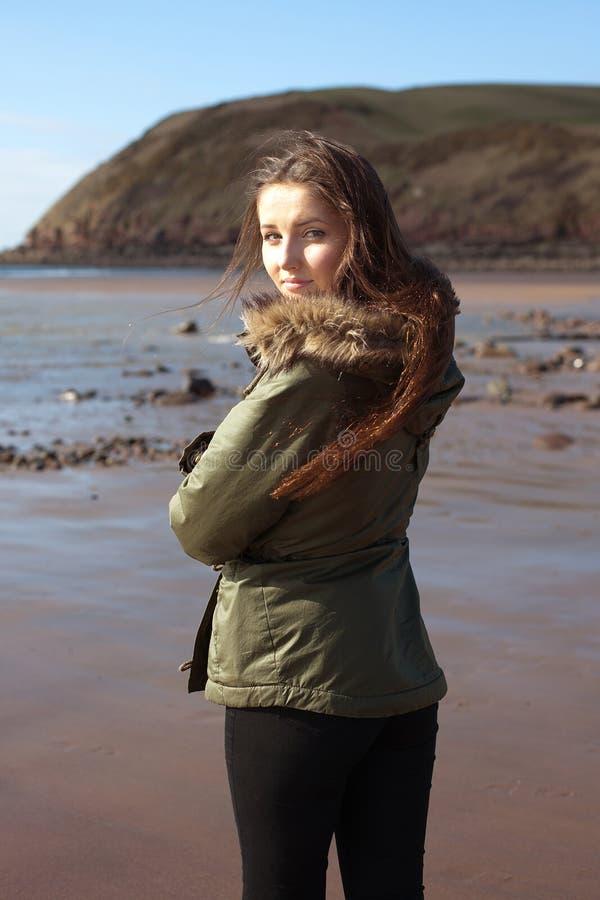 Junge Frau am Strand ganz eingewickelt oben gegen den Wind lizenzfreies stockbild