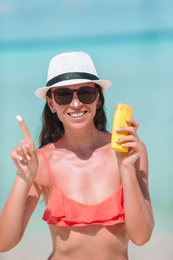 Junge Frau tragen Creme auf ihrer Nase am Strand auf stockfoto