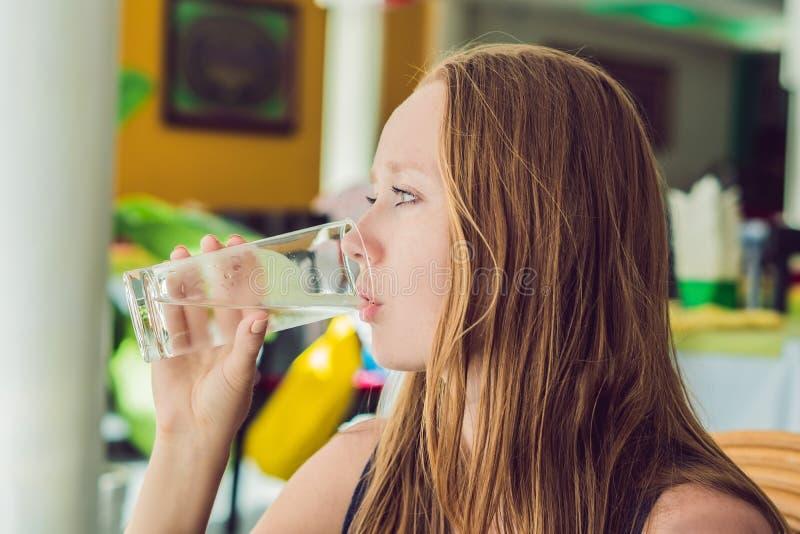Junge Frau trinkt Wasser in einem Café lizenzfreie stockfotografie