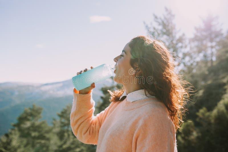 Junge Frau trinkt Wasser mitten in dem Berg stockbilder