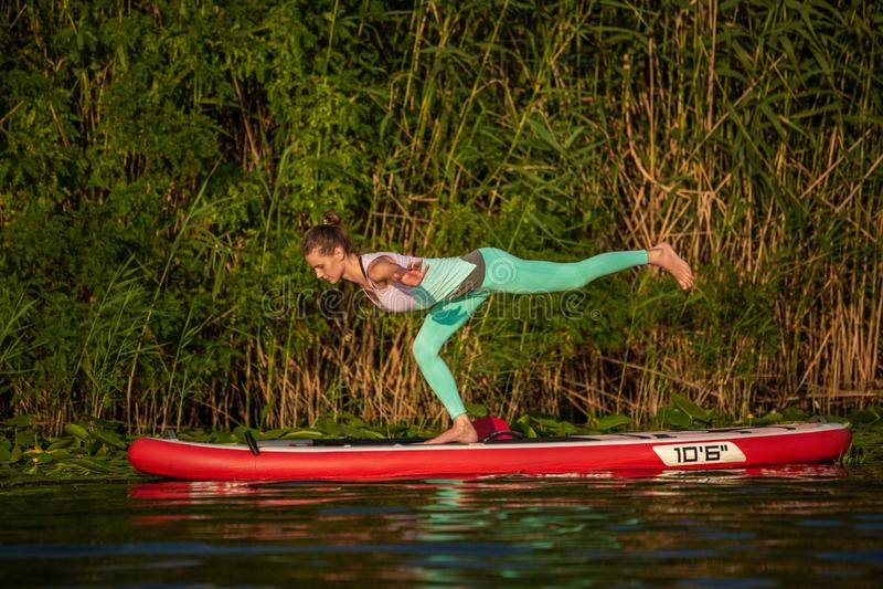 Junge Frau tun Yoga auf einer Radschaufel des Stands oben DINIEREN auf einem schönen See oder einem Fluss stockbild