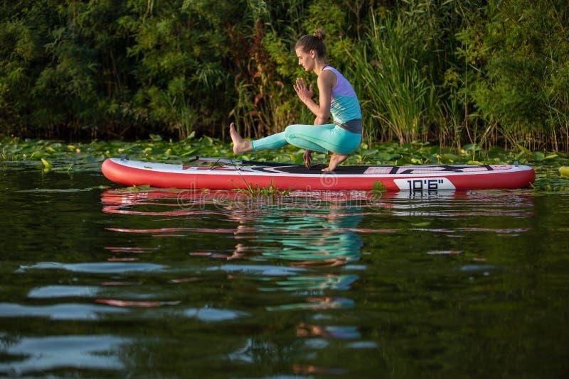 Junge Frau tun Yoga auf einer Radschaufel des Stands oben DINIEREN auf einem schönen See oder einem Fluss lizenzfreies stockfoto