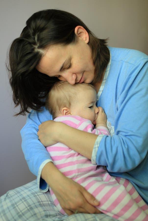 Junge Frau umarmen ihr reizendes Baby stockfotos