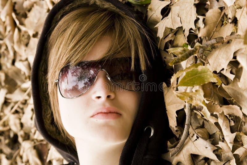 Junge Frau umgeben durch Herbstblätter stockfotos