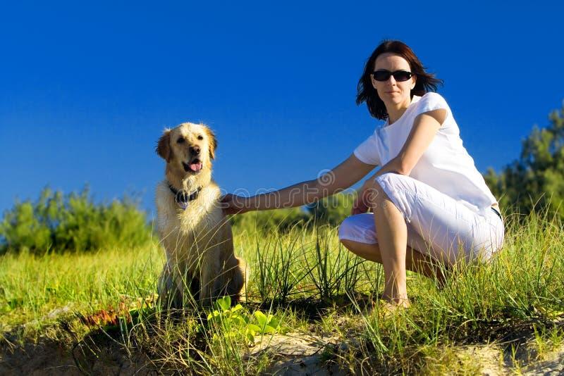 Junge Frau und ein Hundesitzen lizenzfreie stockfotografie