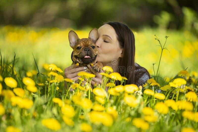 Junge Frau und ein Welpe der französischen Bulldogge stehen in einem Park still stockbilder