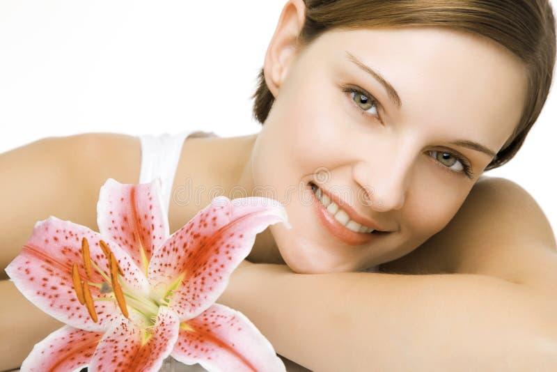 Junge Frau und eine Lilie lizenzfreies stockfoto