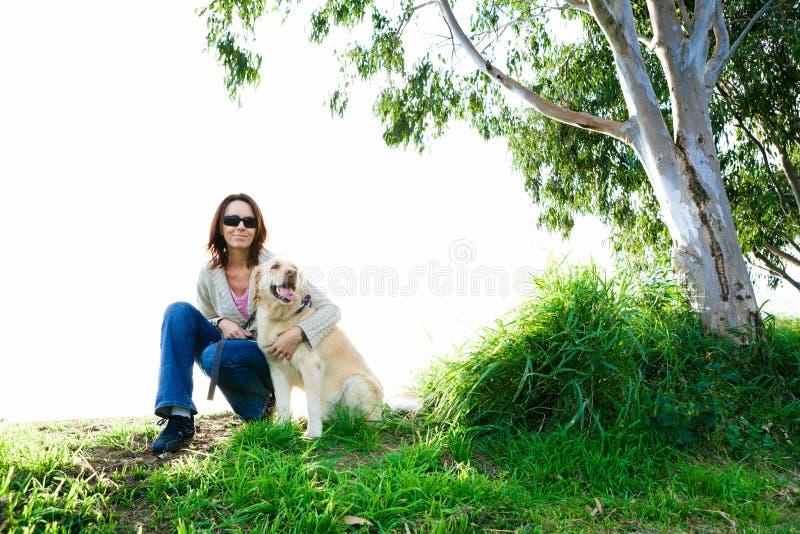 Junge Frau und goldener Apportierhund im Gras stockbild