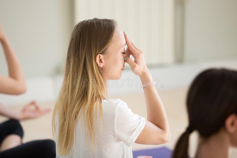 Junge Frau und Gruppe von Personen, die abwechselndes Nasenloch Breathin tut lizenzfreie stockbilder