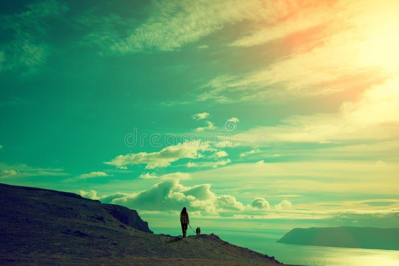 Junge Frau und Hund gegen Seefjord bei Sonnenuntergang stockfoto
