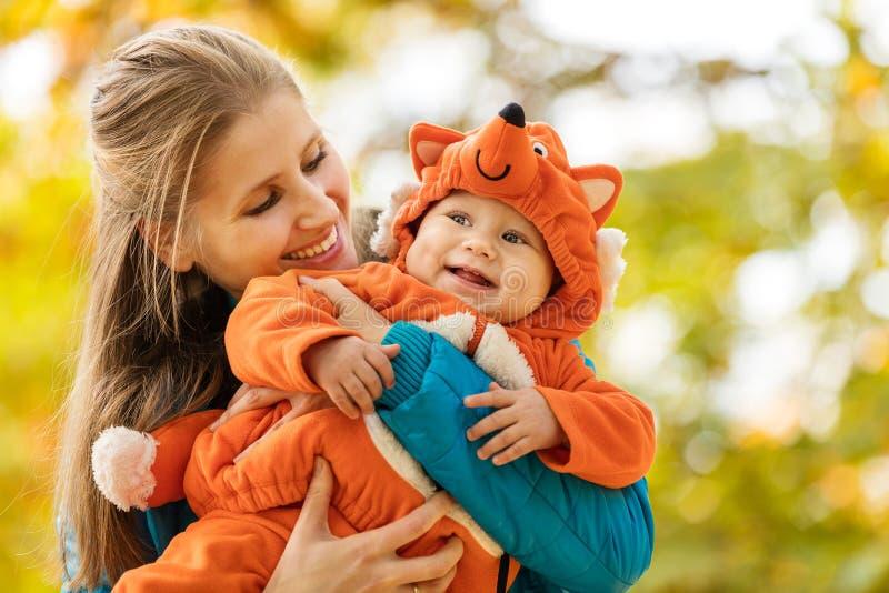 Junge Frau und ihr Babysohn im Herbst parken lizenzfreie stockfotos